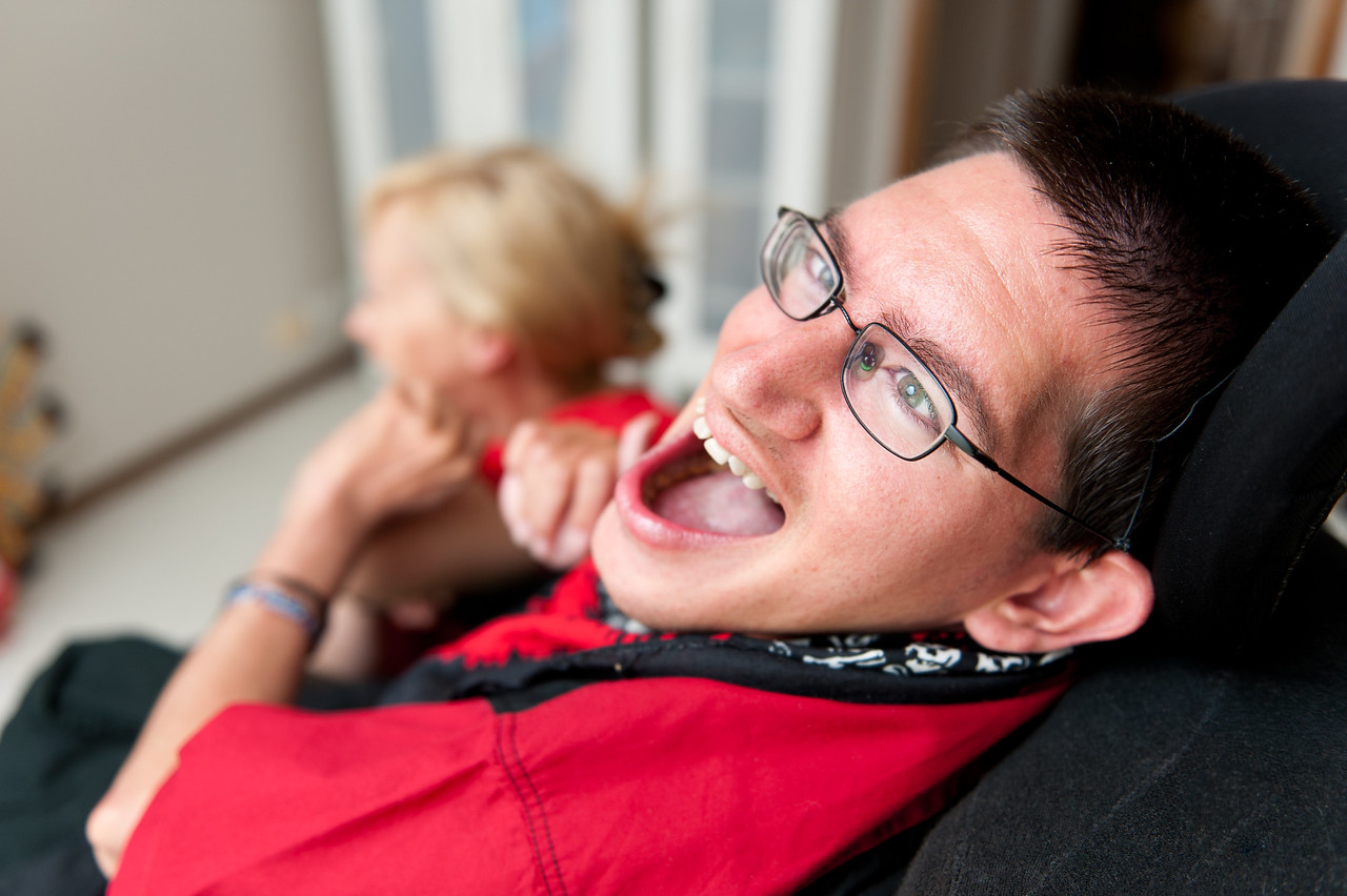 A young man sharing a laugh with his Support Worker, with the man in focus