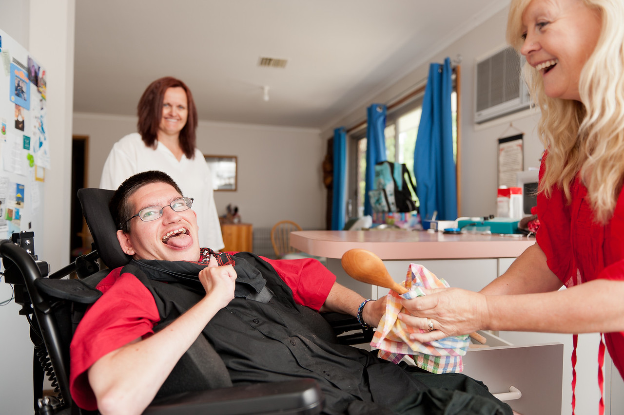 Young man being assisted to wipe dry a wooden spoon by his support worker (with his mother in the background).