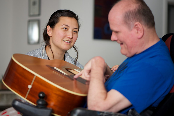 "This photo was made at the man's home, where he was participating in a music session with a staff member.    This photo can be used to illustrate the importance of promoting engagement in meaningful activity.  This whole concept and practice has been referred to as Person-Centred Active Support and has extensive empirical evidence to support its importance in promoting a great quality of life for all people with a disability, ""irrespective of degree of disability or the presence of extra problems*  * Mansell, J., Beadle-Brown, J., Ashman, B., & Ockenden, J. (2004). Person-Centred Active Support. Pavilion Publishing (Brighton) Ltd.."