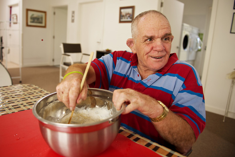 """Senior man with a disability at home mixing flour.  He was cooking muffins for supper in his kitchen.  This photo can be used to illustrate the importance of promoting engagement in meaningful activity.  This whole concept and practice has been referred to as Person-Centred Active Support and has extensive empirical evidence to support its importance in promoting a great quality of life for all people with a disability, """"irrespective of degree of disability or the presence of extra problems*  * Mansell, J., Beadle-Brown, J., Ashman, B., & Ockenden, J. (2004). Person-Centred Active Support. Pavilion Publishing (Brighton) Ltd.."""