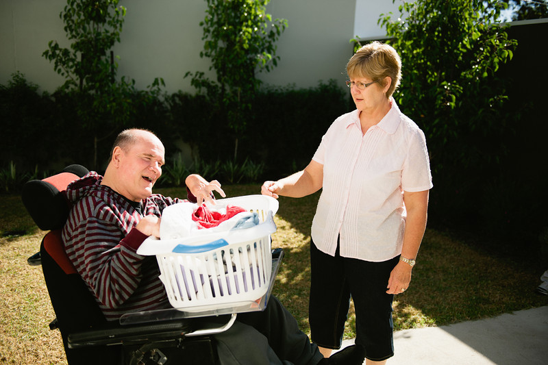 Man in a Wheelchair helping with Hanging out the Washing
