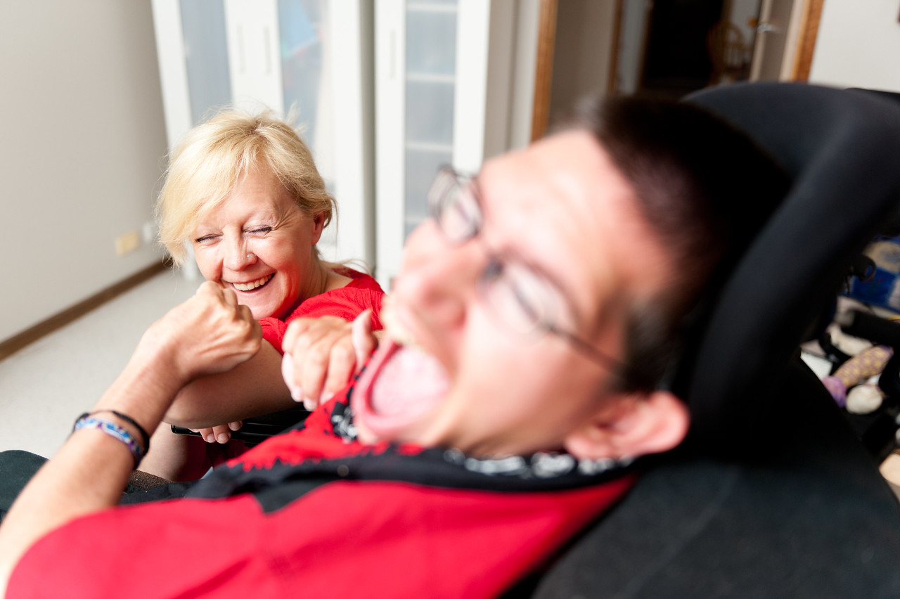 A young man sharing a laugh with his Support Worker, with the woman in focus