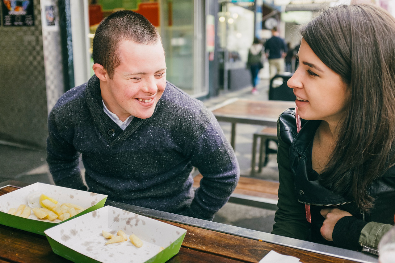 Teenage Boy with Down Syndrome sharing a Laugh with a Young Woman