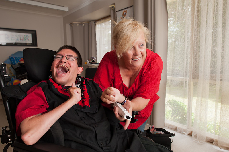 Man laughing heartily  while being assisted by his Support Wroker to play a popular video game