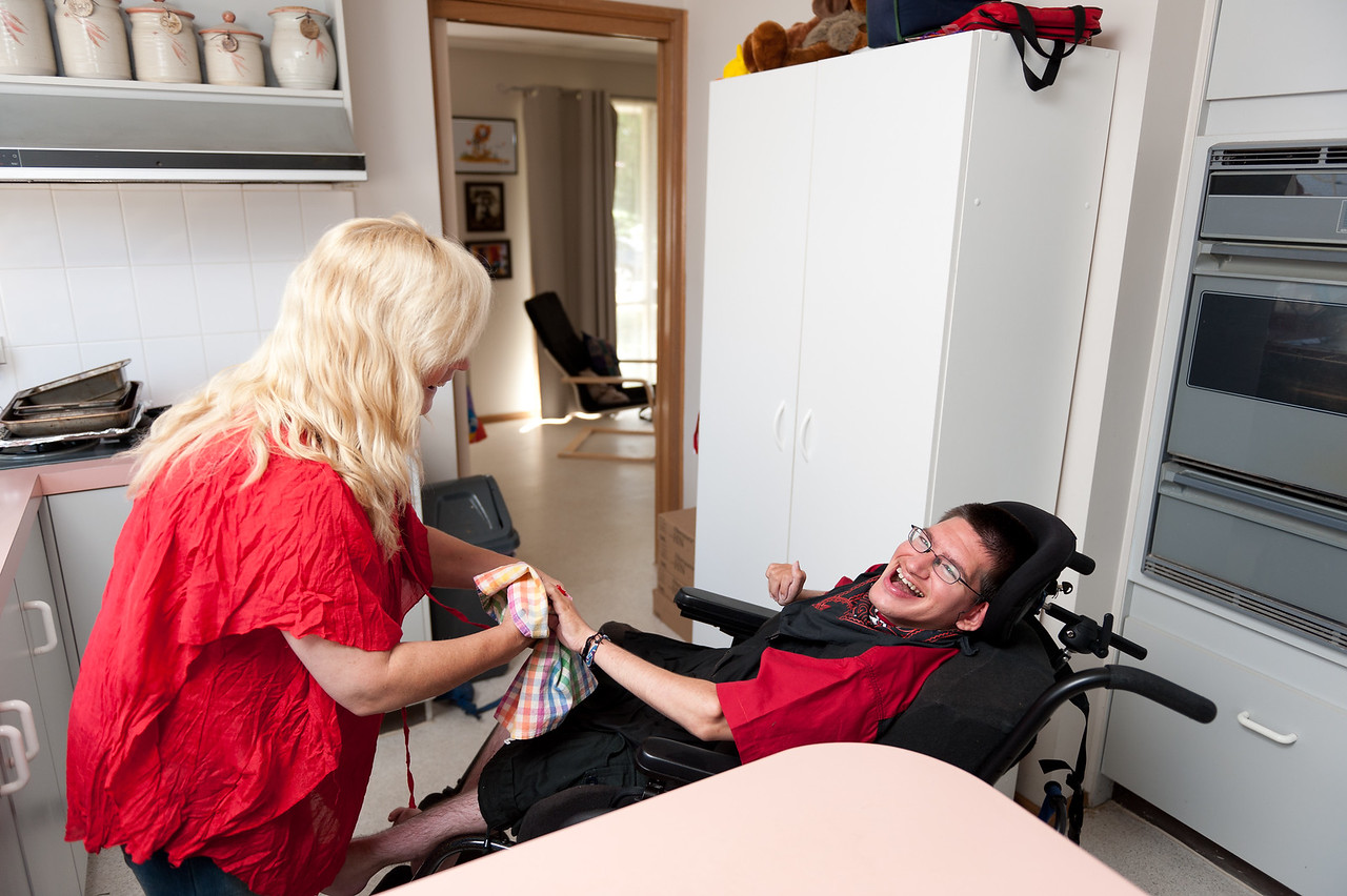 Woman helping a young man to dry dishes.