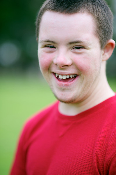 Sixteen-year-old boy with red shirt, smiling at camera