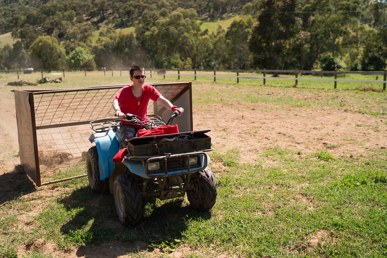 Young Man towing a Feeder with a Quadbike