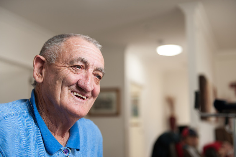 Smiling man in his sixties in his loungeroom.