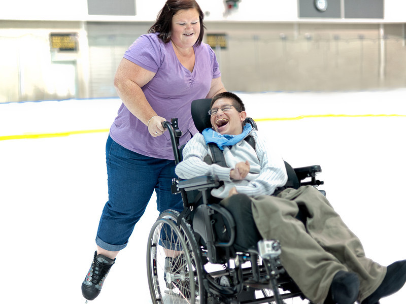 Disability Support Worker pushing a Man on the Ice