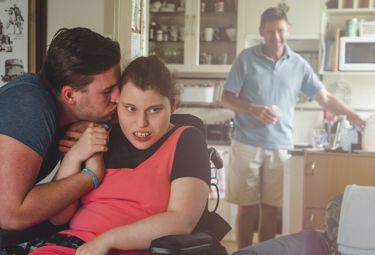 Young Woman with a Disability with her Brother at Home