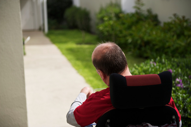 This photo shows the back of a man of 54 in an electric wheelchair going into his backyard