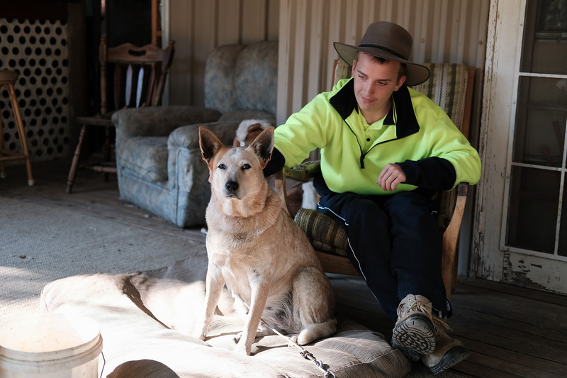 Young Man with a Stock Hat Patting his Dog