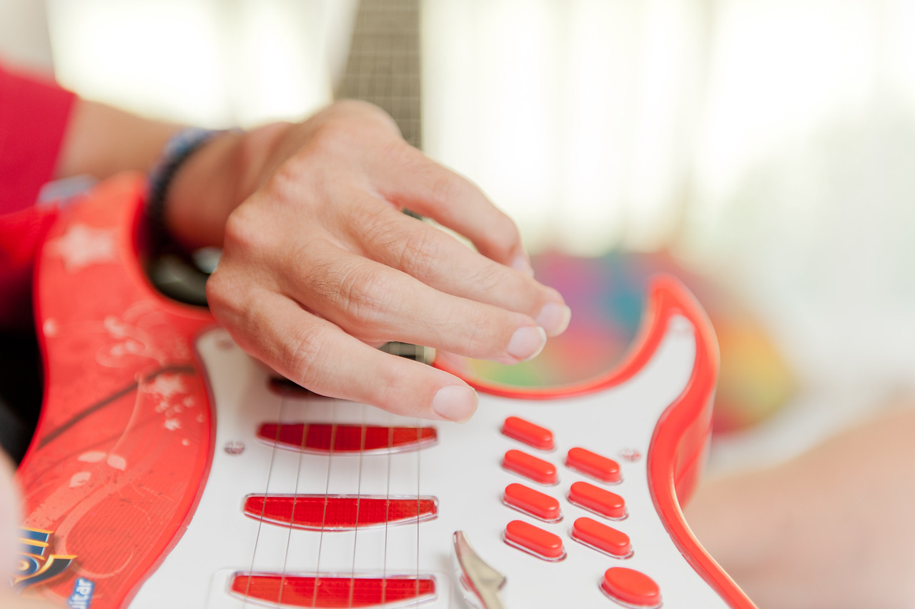 Close up of a Man's hand over a guitar video controller.
