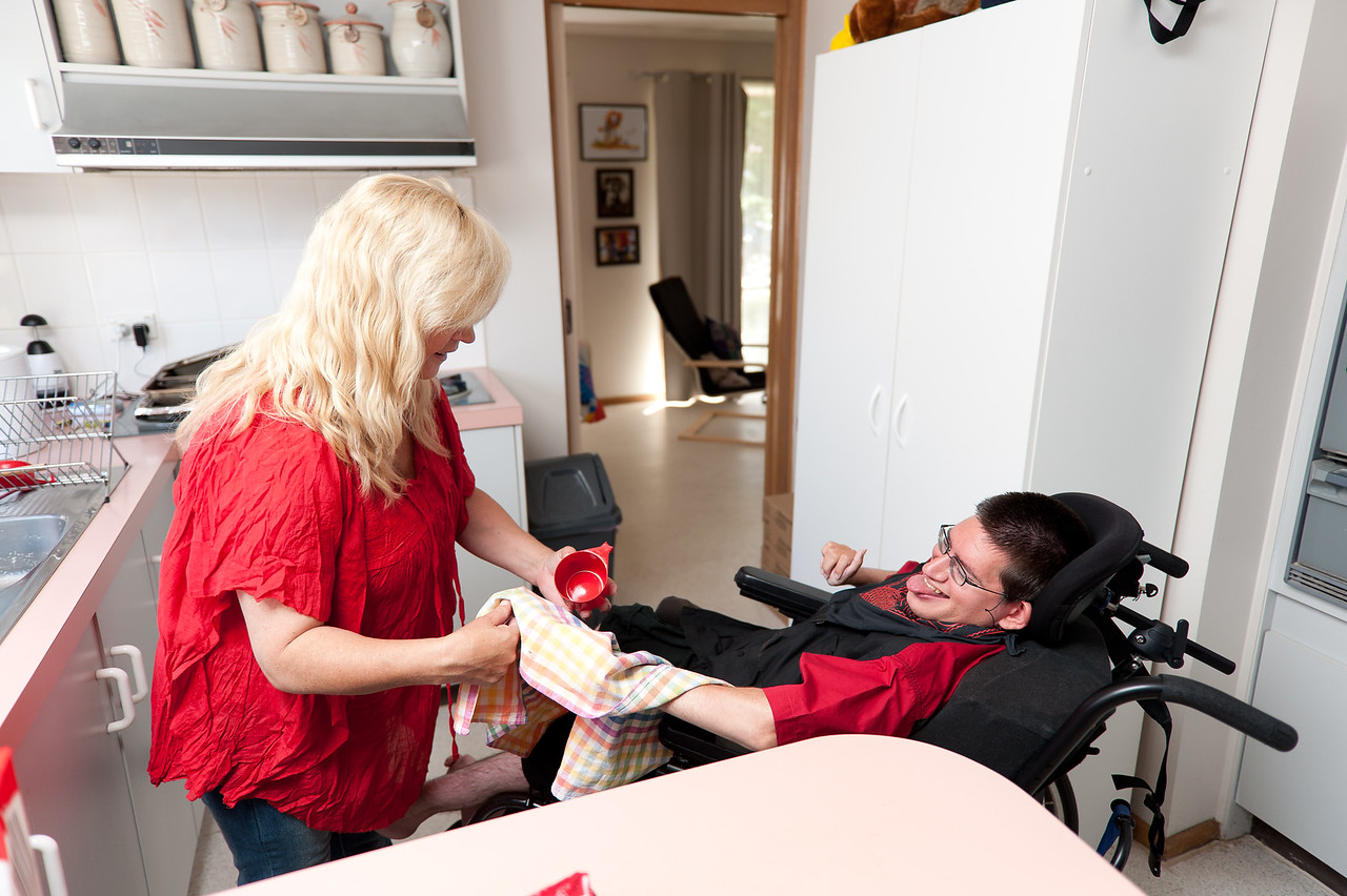 """Woman helping a man to dry dishes.  This photo can be used to illustrate the importance of promoting engagement in meaningful activity.  This whole concept and practice has been referred to as Person-Centred Active Support and has extensive empirical evidence to support its importance in promoting a great quality of life for all people with a disability, """"irrespective of degree of disability or the presence of extra problems*  * Mansell, J., Beadle-Brown, J., Ashman, B., & Ockenden, J. (2004). Person-Centred Active Support. Pavilion Publishing (Brighton) Ltd.."""