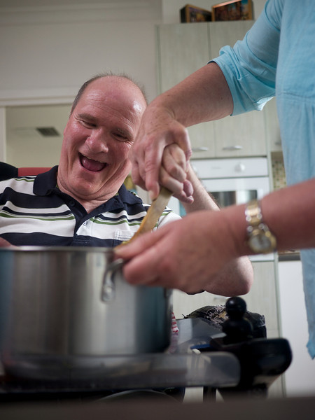 This man, with a disability, is occupied in stirring food in a pot with the assistance of a home carer.