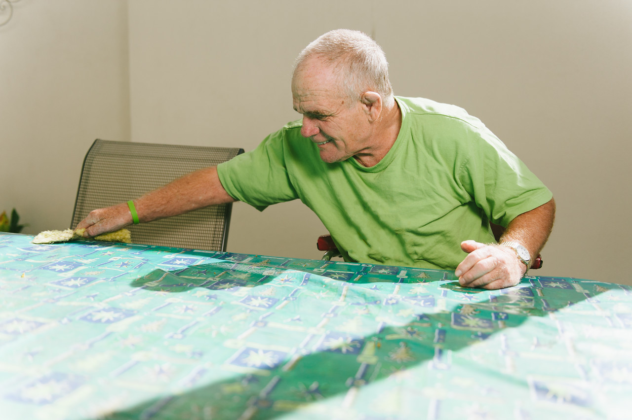 Man with an Intellectual Disability wiping an Outdoor Table