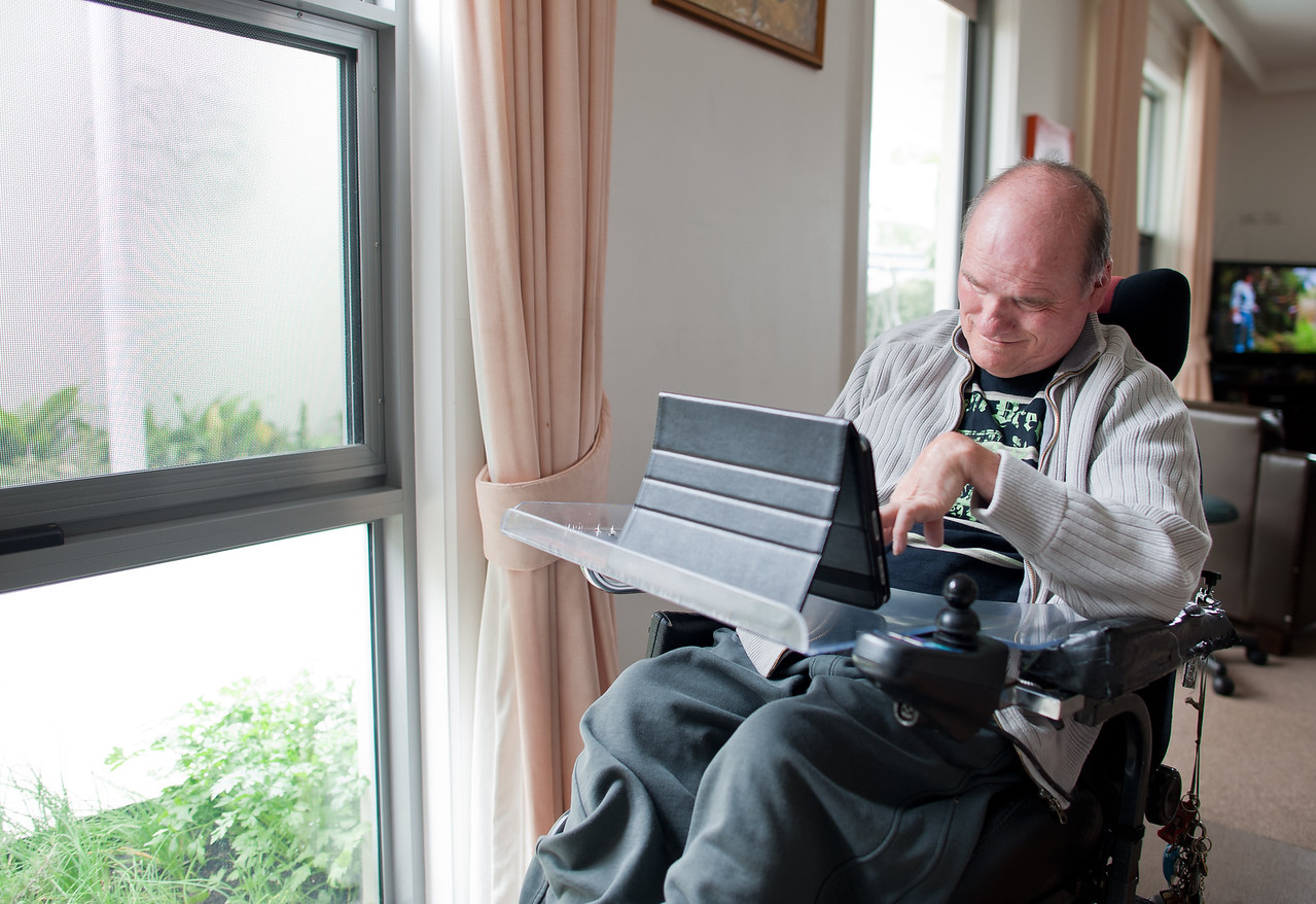 Man with a disability using computer by a window in his living room.