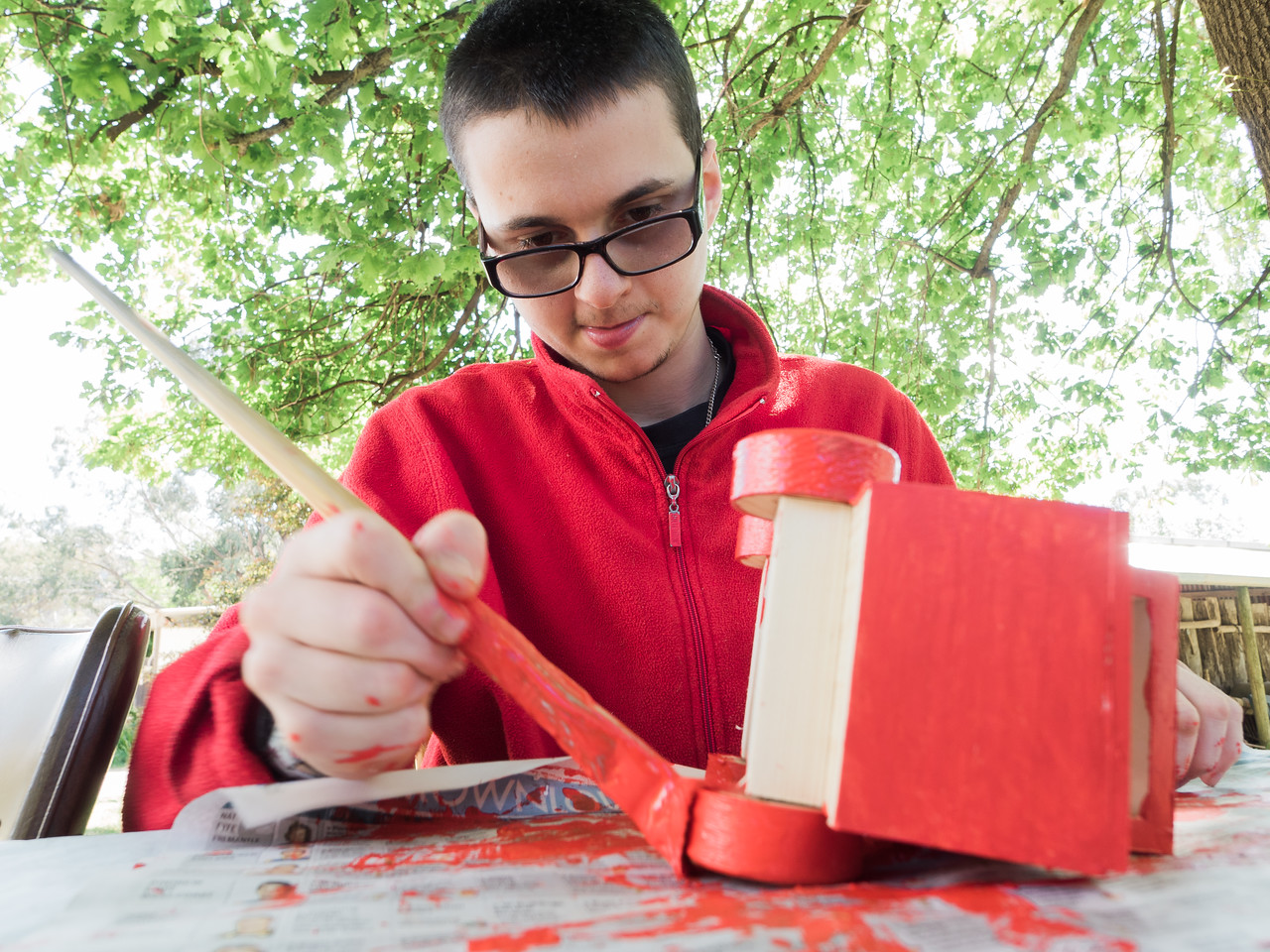 Man painting a wooden toy truck