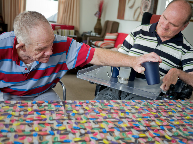 This photo shows one man with a disability taking cups from the wheelchair tray of his housemate.  They were involved cooperatively in setting the table for them and their other housemates.