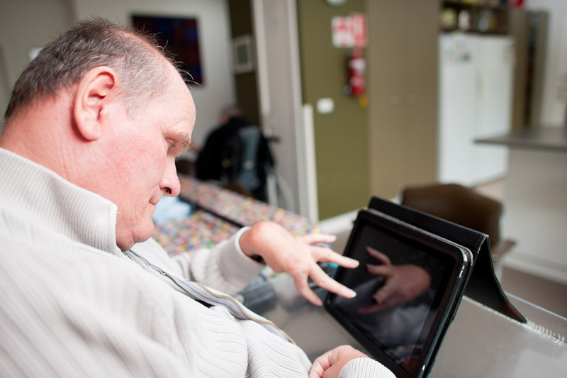 Mature aged man with a disability operating touchscreen computer.  The reflection of his hand can be seen on the screen.  He is seated in his living room.