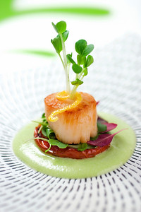 A delectable appetizer of pan seared jumbo sea scallop set atop an oven roasted thyme seasoned campari tomato with micro green in a citrus dill soybean puree.  garnished with lemon and daikon sprouts.  Shallow dof.