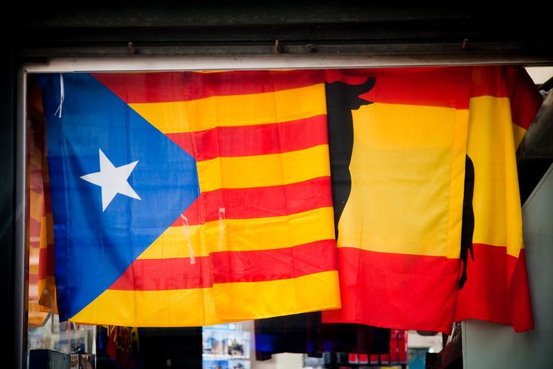 La bandera independentista catalana junto a una española en un kiosco de las Ramblas, Barcelona