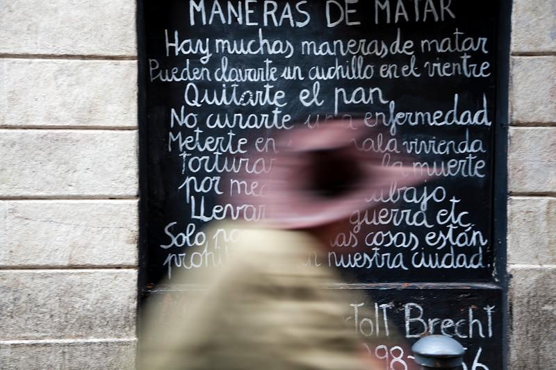 Un hombre con sombrero pasa ante una pared pintada con un poema de Bertold Brecht, calle Tallers, Barcelona