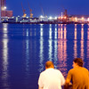 Dos hombres sentados frente al mar en el paseo de Colón, puerto de Barcelona