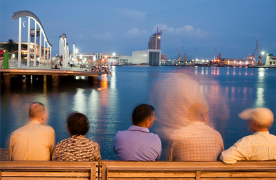 Ciudadanos en un banco del paseo de Colón, frente al Puerto de Barcelona