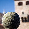 Ornamental granite ball with the tower of Golfines de Abajo palace on the background, San Jorge square, Caceres, Spain