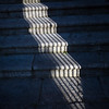 The shadow of a window grille on stone steps, Caceres, Spain