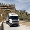A modern truck going through the triumphal arch of Alcantara bridge, a Roman building ended in 106 AD, Caceres, Spain