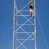Man at work on a scaffolding against a clear, blue sky.