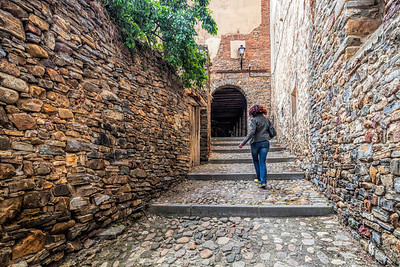 Young woman climbing a stone stair in the old town of Yanguas, Soria, Spain