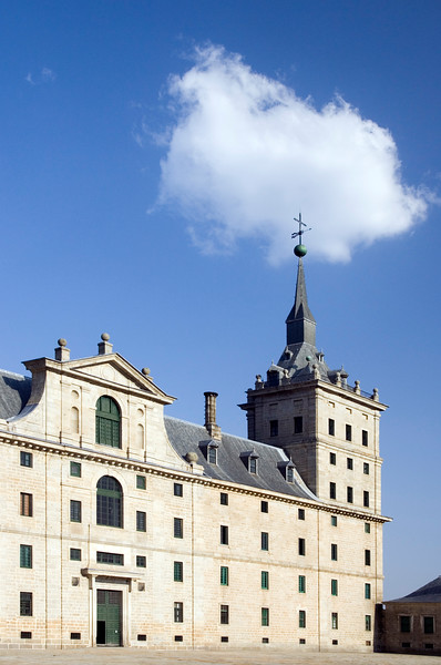 Partial view of El Escorial facade with a white cloud over a tower.