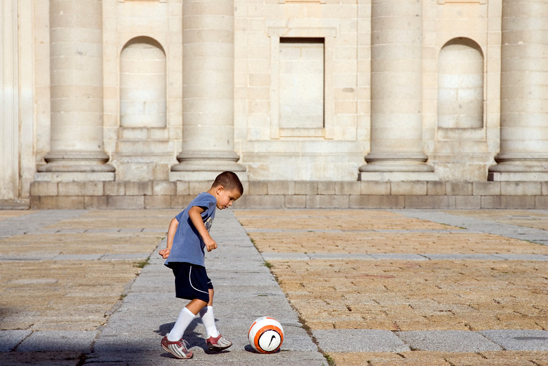 A child playing football in front of El Escorial facade, Spain