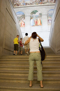 """A visitor taking photos at El Escorial staircase, Spain. The staircase was made by Giambattista Castello, called """"Il Bergamasco"""" (16th century). The fresco paintings are a work by the Spanish painter Lucas Jordan (17th century)"""