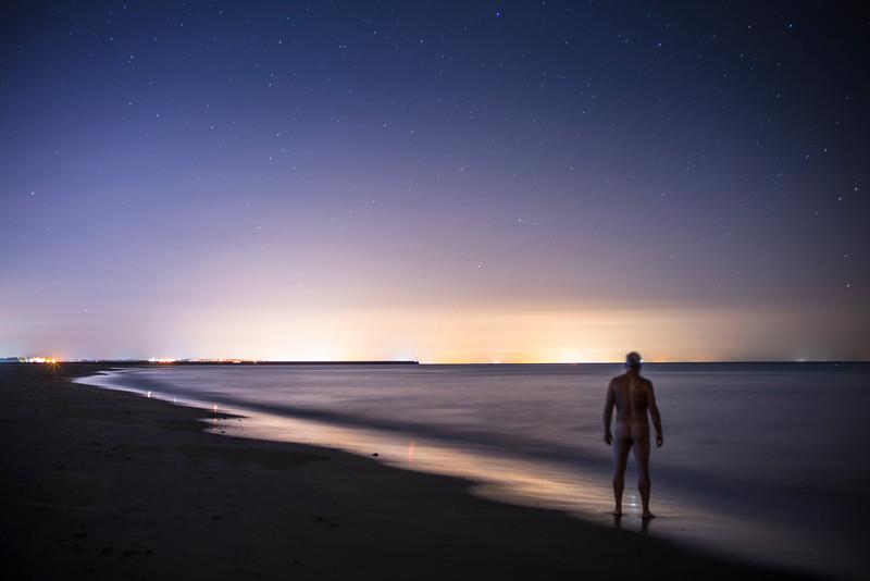 Naked man staring at the sea by night. Punta del Moral, Ayamonte, Spain.