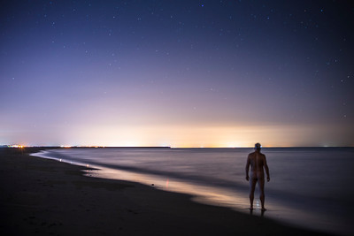 Naked man staring at the sea by night. Punta del Moral, Ayamonte, Spain.