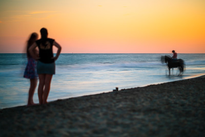 Two women contemplating a horseman on the beach at sunset, Ayamonte, Spain.