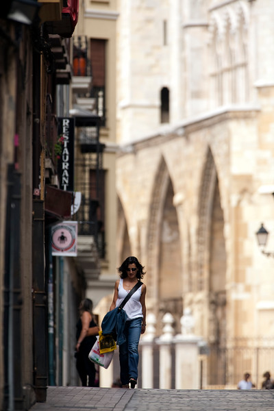 A girl walking down the street with the Cathedral on the background, town of Leon, autonomous community of Castilla y Leon, northern Spain