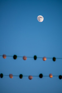 Waxing gibbous moon over two lines of paper lanterns during a festival, Seville, Spain.