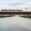 Panning shot of a train over the Guadalquivir river, San Juan de Aznalfarache, Seville, Spain
