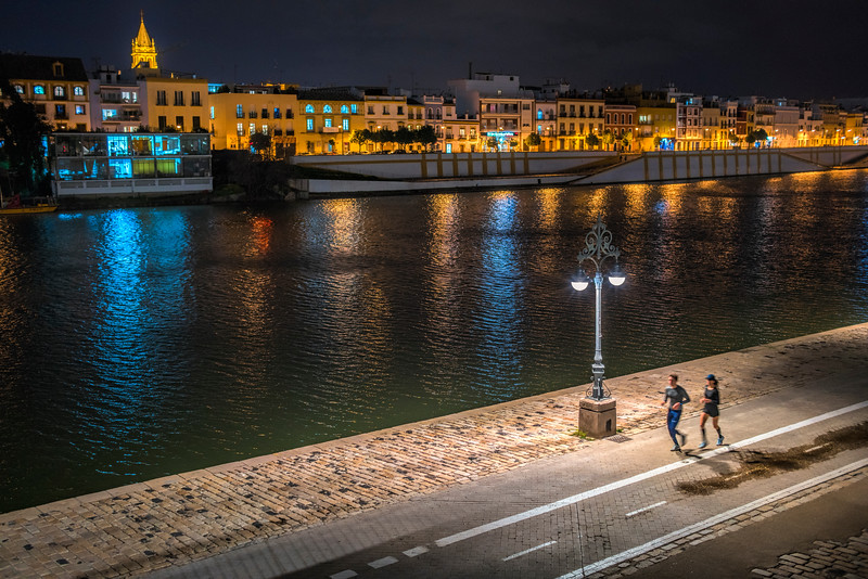 Couple running by the river, Seville, Spain