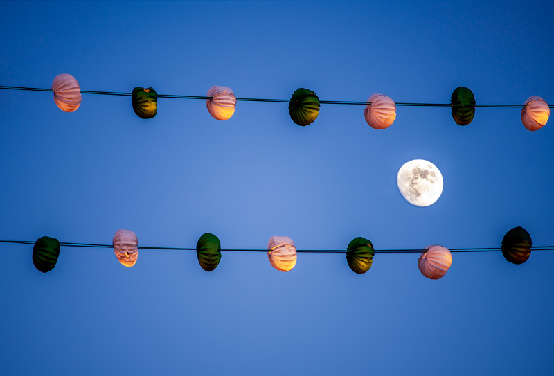Waxing gibbous moon between two lines of paper lanterns during a festival, Seville, Spain.