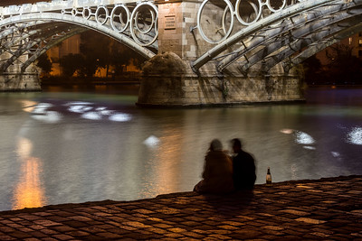 Young couple drinking sparkling wine by the Guadalquivir river and the Triana bridge, Seville, Spain