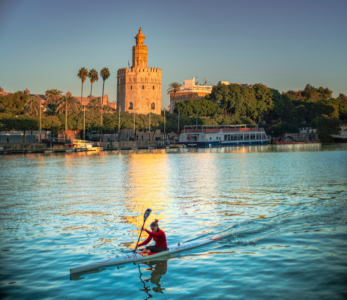 Canoeist on the Guadalquivir river, in front of the Tower of Gold (12th century landmark), Seville, Spain.