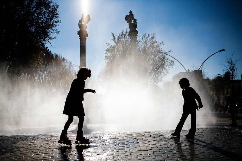 Little girls playing in front of a fountain, Alameda de Hercules square, Seville, Spain