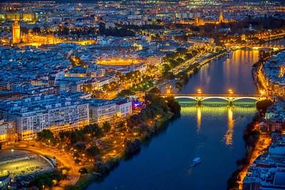Aerial view of downtown Seville at night, showing some of the main landmarks: Triana bridge, Guadalquivir river, Cathedral, Giralda tower, Maestranza bullring, Torre del Oro, Plaza de España...