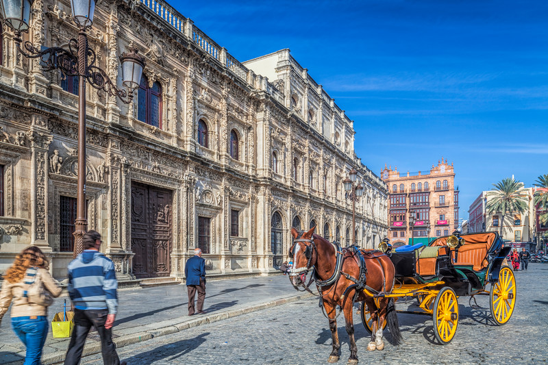 Horse drawn carriage waiting for visitors in front of the plateresque City Hall, San Francisco Square, Seville, Spain